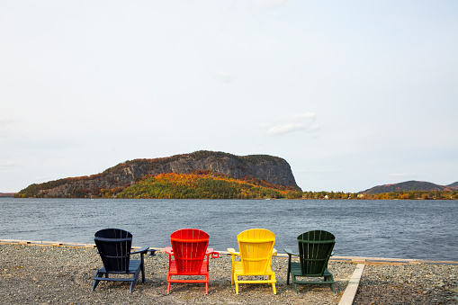 Real Life「Primary colored adirondack chairs facing beautiful lake and mountain scene during the fall」:スマホ壁紙(0)