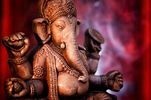 A statue of Ganesha, a deity of India on red background:スマホ壁紙(壁紙.com)