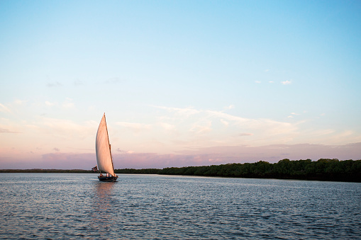 Unrecognizable Person「LAMU, INDIAN OCEAN, KENYA, AFRICA. A wooden dhow sailboat cuts across calm water at sunset.」:スマホ壁紙(14)