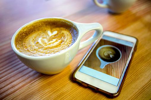 ハート「それのスマート携帯電話写真付きのテーブルでラテ」:スマホ壁紙(1)