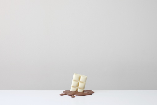 Melting「Conceptual bar of white chocolate in a pool of melted milk chocolate」:スマホ壁紙(6)