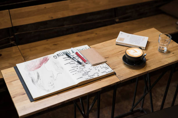 Table in a cafe with coffee mug, notebooks, pens and a glass of water:スマホ壁紙(壁紙.com)