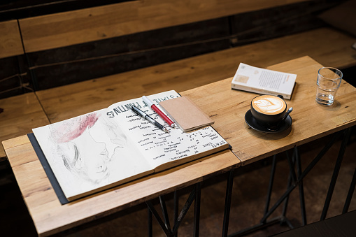 Cappuccino「Table in a cafe with coffee mug, notebooks, pens and a glass of water」:スマホ壁紙(16)