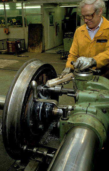 Industrial Laborer「A machinist applies cutting oil to the tool during the refurbishment of wheel sets on a lethe at Wolverton Works」:写真・画像(15)[壁紙.com]