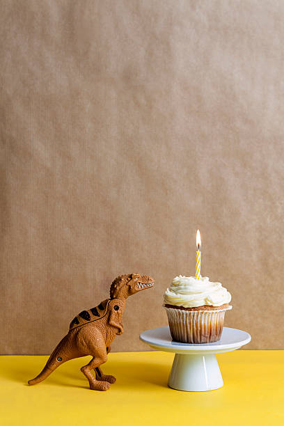 Toy dinosaur and cup cake with lighted candle on a cake stand:スマホ壁紙(壁紙.com)