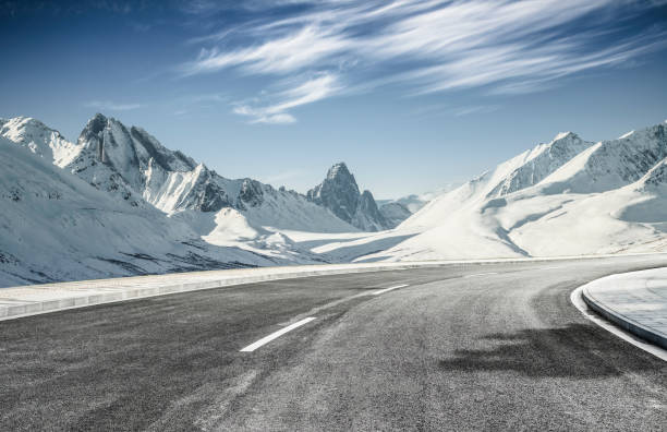 empty asphalt road leading towards snow mountains:スマホ壁紙(壁紙.com)