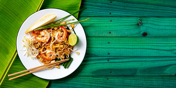 World famous Thai recipe of Prawn Pad Thai noodles with chopsticks on a dish and banana leaf on a turquoise colored old wood panel table background.:スマホ壁紙(壁紙.com)