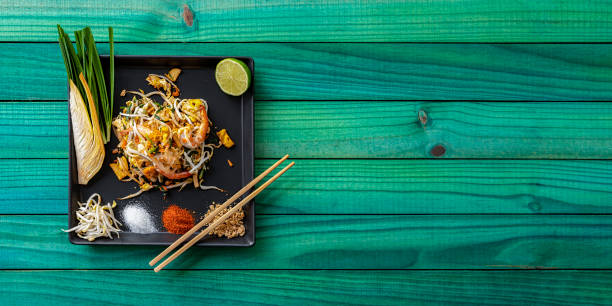 World famous Thai recipe of Prawn Pad Thai noodles with chopsticks on a dish and banana leaf on an old turquoise wood panel table background.:スマホ壁紙(壁紙.com)