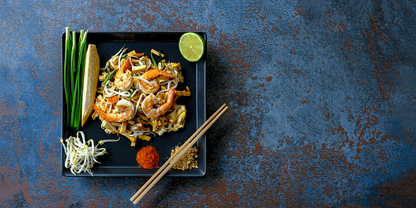 PGA Event「World famous Thai recipe of Prawn Pad Thai noodles with chopsticks on a dish on a textured blue colored abstract panel table background.」:スマホ壁紙(6)
