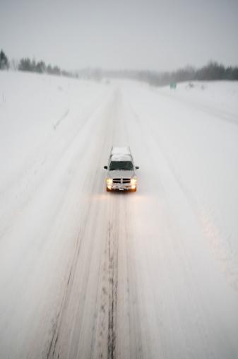雪「A lone vehicle driving on a snowy highway.」:スマホ壁紙(10)