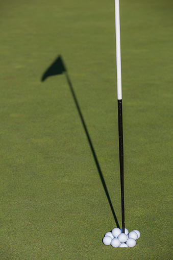 Taking a Shot - Sport「Golf balls overflowing a golf hole.」:スマホ壁紙(12)
