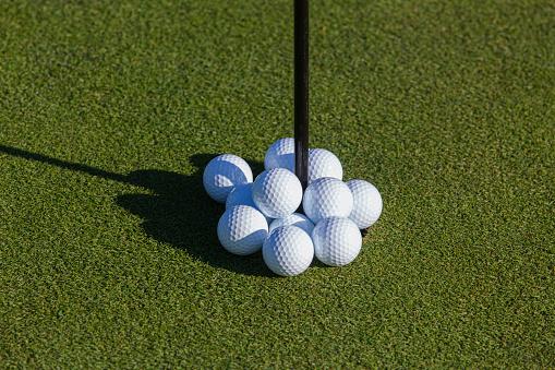 Taking a Shot - Sport「Golf balls overflowing a golf hole.」:スマホ壁紙(1)