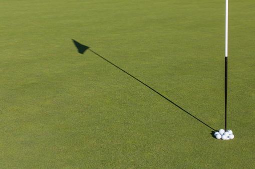 Taking a Shot - Sport「Golf balls overflowing a golf hole.」:スマホ壁紙(10)