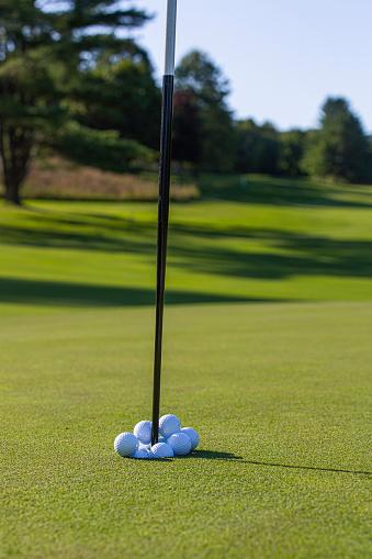Taking a Shot - Sport「Golf balls overflowing a golf hole.」:スマホ壁紙(19)