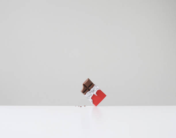 Chocolate bar with missing bite and chocolate crumbs on table:スマホ壁紙(壁紙.com)