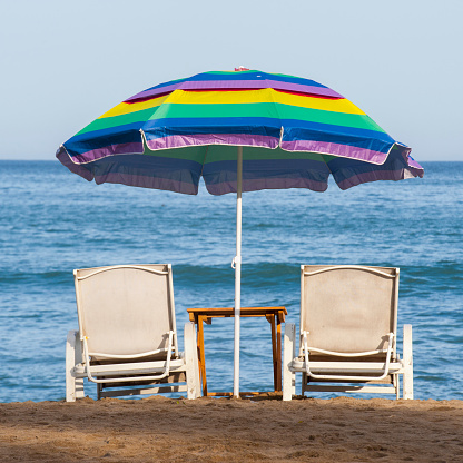 Sayulita「A rainbow beach umbrella over two lounge chairs on the beach at the water's edge; sayulita mexico」:スマホ壁紙(0)