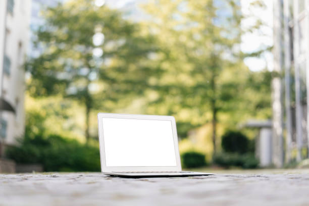 Laptop on cobblestones in park with office buildings in background:スマホ壁紙(壁紙.com)