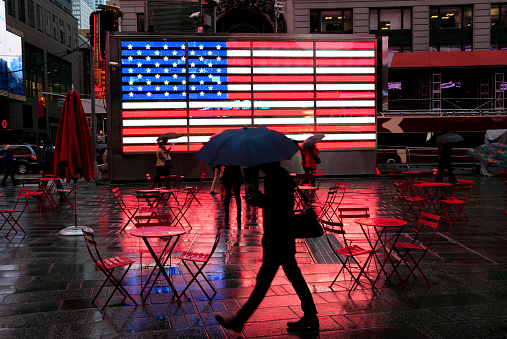 Unrecognizable Person「City in the Rain: silhouette of pedestrian with umbrella passing famous flag in wet Times Square」:スマホ壁紙(3)
