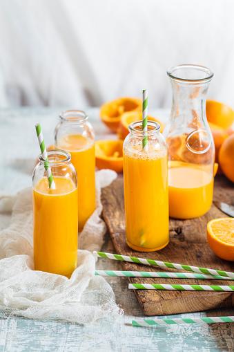 Juice - Drink「Sliced oranges and glass bottles of freshly squeezed orange juice」:スマホ壁紙(15)