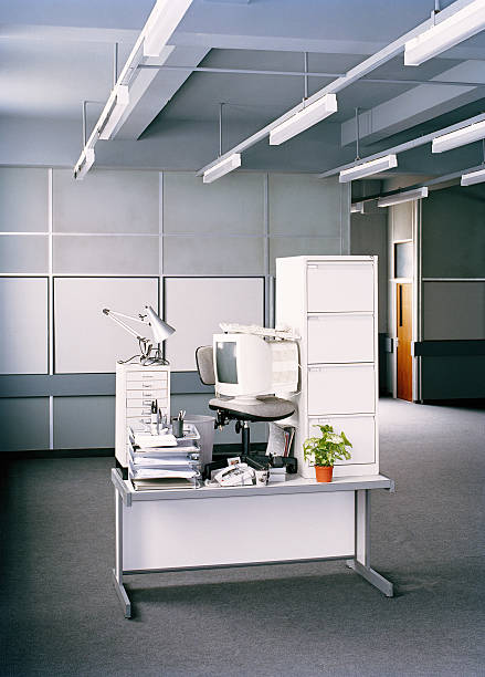 Office equipment and personal belongings stacked on desk:スマホ壁紙(壁紙.com)