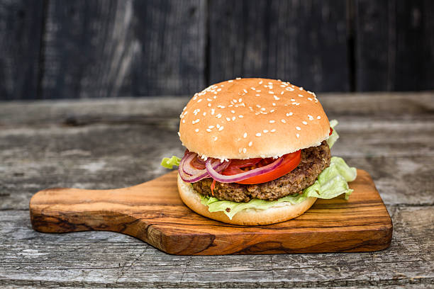 Homemade burger with lettuce, meat, tomato and onion on chopping board:スマホ壁紙(壁紙.com)