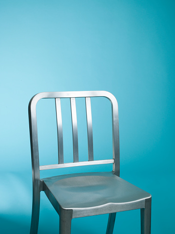 寂しさ「Empty metal chair against a bright blue background」:スマホ壁紙(1)