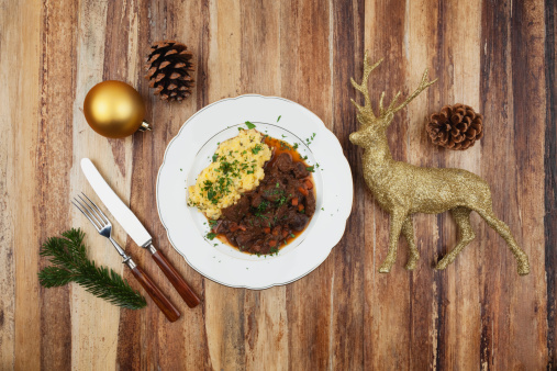 Venison「Plate of cooked venison goulash with mashed potatoes and Christmas decoration on wooden background」:スマホ壁紙(16)