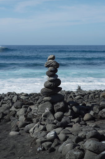ビーチ「A stack of grey stones balanced on top of each other on stoney beach with black sand」:スマホ壁紙(15)