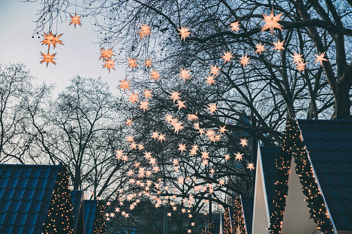 Market Stall「Decoration of paper stars on trees over roofs of the Christmas Market during dusk」:スマホ壁紙(8)