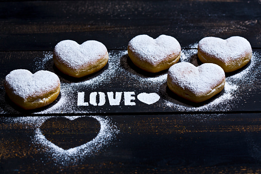 Sprinkling「The word 'Love' stenciled with icing sugar and five heart-shaped crullers on dark wood」:スマホ壁紙(19)