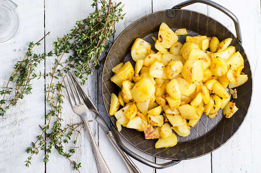 Cast Iron「Cast iron frying pan of fried potatoes, thyme and cutlery on wood」:スマホ壁紙(5)