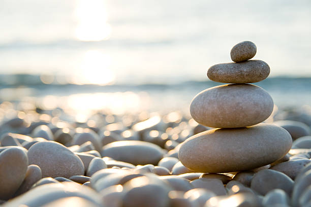 Balanced stones on a pebble beach during sunset.:スマホ壁紙(壁紙.com)