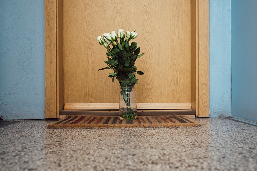 Consoling「Vase with farewell flowers on floor mat at apartment door of deceased neighbour」:スマホ壁紙(3)