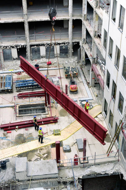 Overview of construction site showing a tower crane lifting a steel girder.:ニュース(壁紙.com)