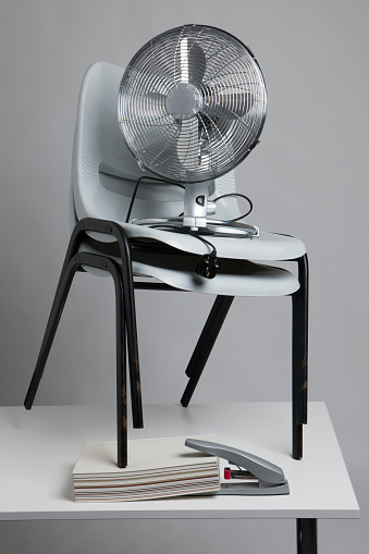 Effort「Grey stacking chairs on an office desk with a fan on top」:スマホ壁紙(11)