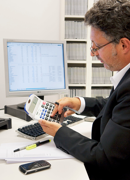 Financial Advisor「Accountant at his desk working with calculator」:写真・画像(9)[壁紙.com]