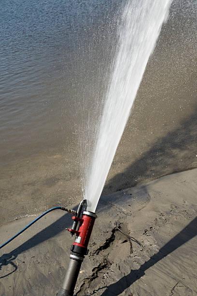 Hose from a fire truck spraying water into a river:スマホ壁紙(壁紙.com)