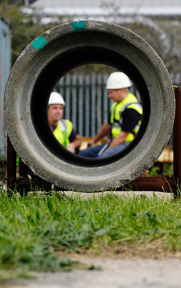 Grass Family「Large concrete utility pipe on a construction yard with workers in background」:写真・画像(11)[壁紙.com]