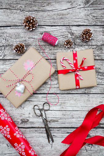 Tradition「Wrapped Christmas presents, fir cones, ribbon and scissors on wood」:スマホ壁紙(0)