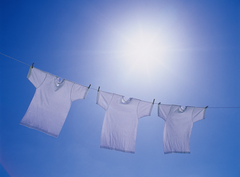 Laundry「Three T-shirts being hanged out under blue sky, blue background」:スマホ壁紙(15)