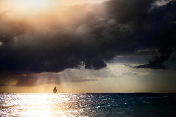 Sunbeams through storm clouds over sailboat:スマホ壁紙(壁紙.com)