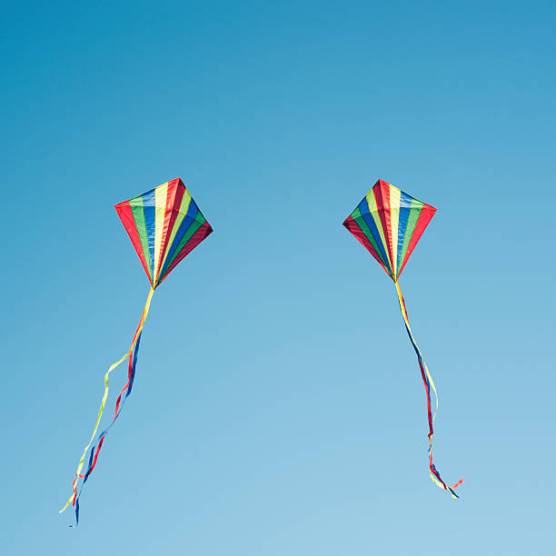 Two colourful kites flying in blue sky:スマホ壁紙(壁紙.com)