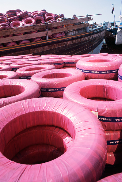 Dubai Creek「Pink wrapped tyres piled high on the quay for loading onto a Gulf trading show in Dubai creek harbour」:写真・画像(8)[壁紙.com]