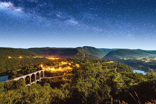 Multiple Exposure「High angle view of french Bugey mountains beginning of Jura landscape by summer night with old stone railway viaduct arch bridge crossing Ain river and beautiful star sky」:スマホ壁紙(17)
