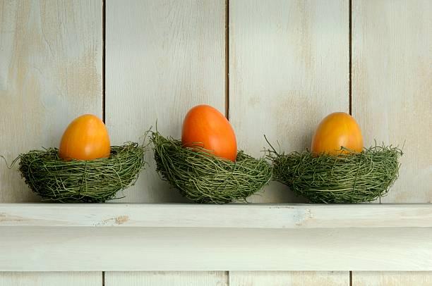 Orange Easter eggs lying in nest on shelf:スマホ壁紙(壁紙.com)
