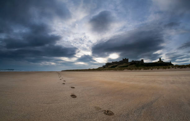 A Single Set Of Footprints On The Beach With Bamburgh Castle In The Background:スマホ壁紙(壁紙.com)