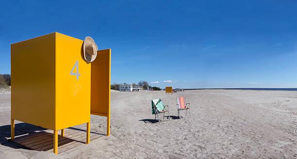 Estonia, Parnu, yellow changing cubicle and two folding chairs on empty sandy beach:スマホ壁紙(壁紙.com)