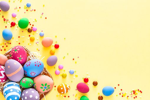 Easter Basket「Colorful Easter eggs with candies and sugar sprinkles on yellow background. Copy space」:スマホ壁紙(2)