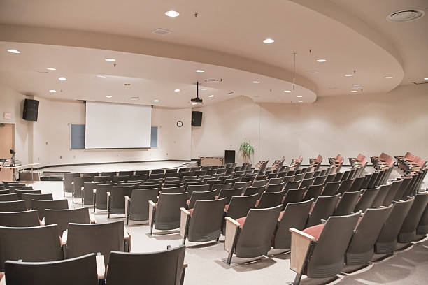 Empty lecture hall with several rows of seats and a screen:スマホ壁紙(壁紙.com)