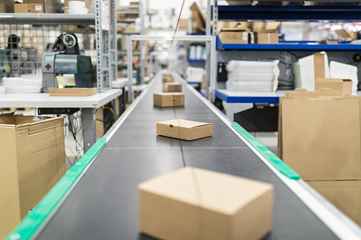 In A Row「Cardboard boxes on conveyor belt at distribution warehouse」:スマホ壁紙(2)